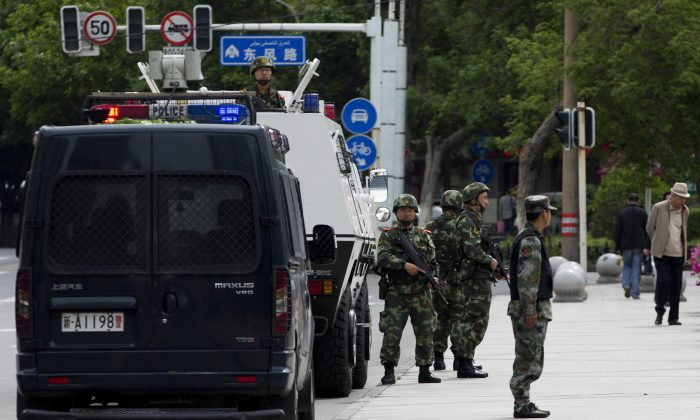 In this Friday, May 23, 2014 photo, armed Paramilitary policemen stand guard next to their Armored personnel carrier parked near the People's Square in Urumqi, in China's northwestern province of Xinjiang. A human rights group says 100,000 Chinese troops are headed to the restive province. (AP Photo/Andy Wong)
