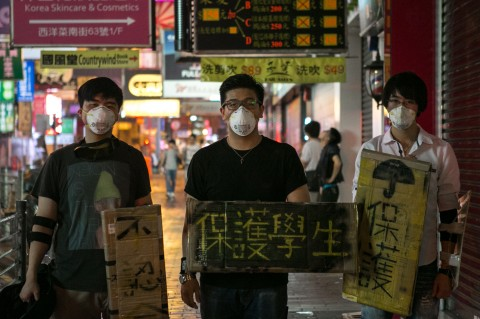 Pro-democracy protesters wear masks and carry signs shaped as shields in Mong Kok, Hong Kong on Oct. 7. Hacker groups online have been supporting the protesters by launching cyberattacks on the Chinese regime. (Benjamin Chasteen/Epoch Times)