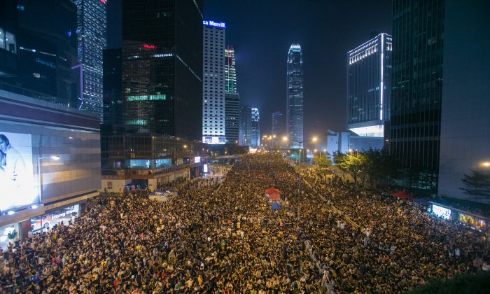 Tens of thousands of people gather on Connaught Road Central on Oct. 4, near the Chinese People's Liberation Army Forces Building. The protesters demand that Chief Executive Chun-ying Leung resign from his position in Hong Kong. (Benjamin Chasteen/Epoch Times)