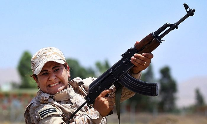 In this Thursday, July 3, 2014 photo, a member of an elite unit of women Kurdish Peshmerga fighters trains in Sulaimaniyah, 160 miles (260 kilometers) northeast of Baghdad, Iraq. Among the Kurdish fighters defending the Syrian town of Kobani against the IS are thousands of women. In April, Kurdish fighters created all-female combat units that have grown to include more than 10,000 women who played a major role in battles against IS, said Nasser Haj Mansour, a defense official in Syria's Kurdish region. (AP Photo)