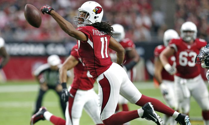 Arizona Cardinals wide receiver Larry Fitzgerald (11) misses a catch against the Philadelphia Eagles during the first half of an NFL football game, Sunday, Oct. 26, 2014, in Glendale, Ariz. (AP Photo/Ross D. Franklin)