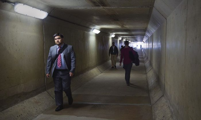 Pentagon workers walk through a pedestrian tunnel in the South Parking lot area that crosses under Interstate 95 highway during an Ebola scare in Washington, DC, on Oct. 17, 2014. Police reopened a building entrance and a parking lot after the brief scare proved baseless, defense officials said. The scare was prompted by a woman who vomited in the parking lot earlier in the day told emergency workers that she had recently visited West Africa, the Defense Department said. (Paul J. Richards/AFP/Getty Images)