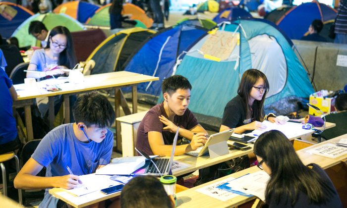 "Students work at what is called the ""Study Corner,"" which was set up by a few activists so students can still do their homework and study while protesting at the same time in the Central District of Hong Kong on Oct. 14, 2014. The study has a generator which provides electricity and also working WiFi for the students. (Benjamin Chasteen/Epoch Times)"