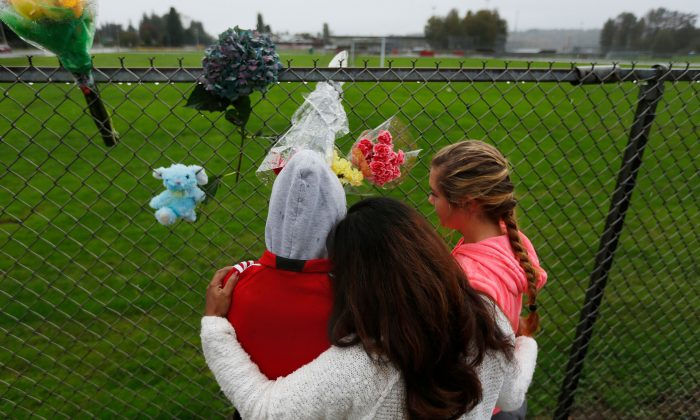 Marysville Pilchuck student Tyanna Davis, left, places flowers with her mother, center, and another student on the fence bordering the high school, Saturday, Oct. 25, 2014. A student opened fire in a high school cafeteria north of Seattle on Friday, killing at least one person and shooting several others in the head, officials said. The gunman also died in the attack. (AP Photo/The Herald, Mark Mulligan)