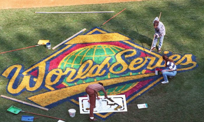 Dick Kunath, Patty Kunath and Ceil Kunath paint World Series sign on the first base side of Yankee Stadium in New York on 17 October. The World Series begins 19 October in New York with the American League champion Yankees playing the National League champions. (STAN HONDA/AFP/Getty Images)