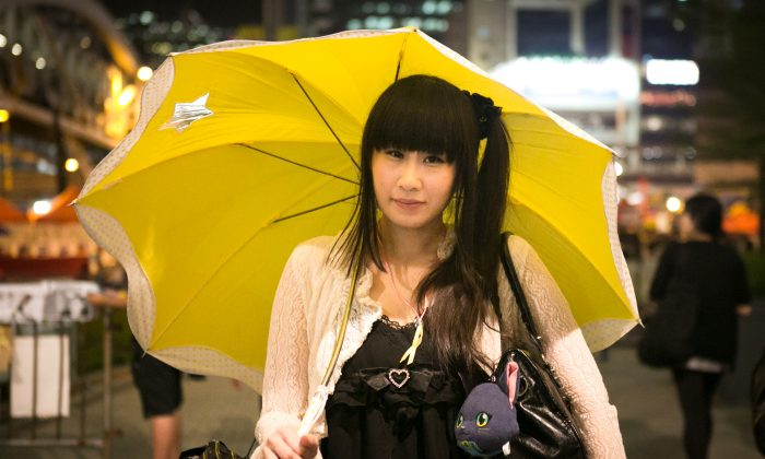 A woman holds a yellow umbrella during a rally on Oct. 28, 2014 marking one month since authorities used tear gas to drive protesters away in the Central District of Hong Kong. (Benjamin Chasteen/Epoch Times)