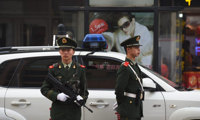 Chinese paramilitary police officers watch over pedestrians in the Wangfujing shopping district in Beijing on Oct. 24, 2014. (Greg Baker/AFP/Getty Images)