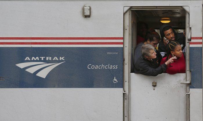 Passengers look at the crash site after an Amtrak train struck a semi-truck about 8:30 a.m. Tuesday, Oct. 28, 2014. (AP Photo/Journal & Courier, John Terhune)