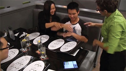 Signs waitstaff teach restaurant patrons to place their order by signing, with help from