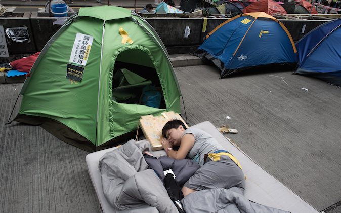 A pro-democracy protester sleeps on a street in the Mongkok district of Hong Kong on October 28, 2014. A month into the mass pro-democracy protests gripping Hong Kong, the movement is under pressure to keep up momentum -- but those on the streets say their vigil has already changed the city for good. (Nicolas Asfouri/AFP/Getty Images)