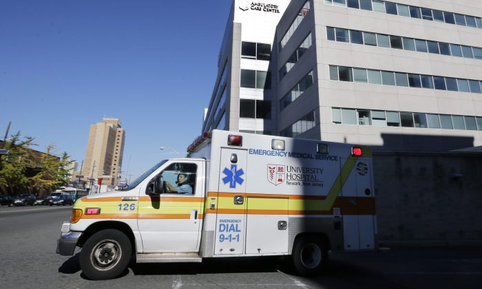 In this Oct. 27, 2014, file photo, an ambulance drives near University Hospital of Newark in Newark, N.J. (AP Photo/Mel Evans)