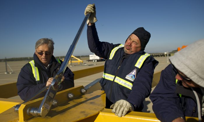 United Space Alliance workers Mike Barnes (L), Pat Floyd, (C), and Chris Kaspar work on assembling part of the sling that will be used to lift space shuttle Discovery off the modified 747 aircraft in Sterling, Va., on April 12, 2012. (Bill Ingalls/NASA via Getty Images)