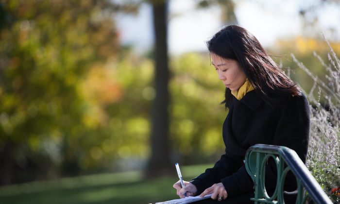 Danielle Wang makes notes before speaking at a press conference calling for her father to be freed, opposite the Chinese Embassy in Washington, D.C., on Oct. 24, 2014. Danielle has worked for 13 years seeking to gain freedom for her father, a prisoner of conscience in China. (Courtesy Danielle Wang)
