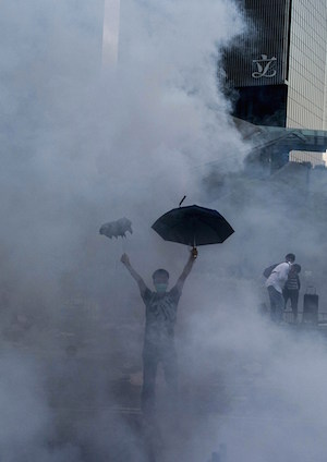 A pro-democracy demonstrator gestures after police fired tear gas towards protesters near the Hong Kong government headquarters on September 28, 2014. (Xaume Olleros/AFP/Getty Images)