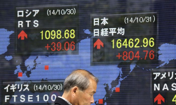 A man walks past an electronic stock board of a securities firm in Tokyo, Friday, Oct. 31, 2014. Japan's Nikkei 225 stock average surged 5 percent and the yen slid against the dollar after the Bank of Japan unexpectedly announced new stimulus to boost a flagging economic recovery. (AP Photo/Eugene Hoshiko)