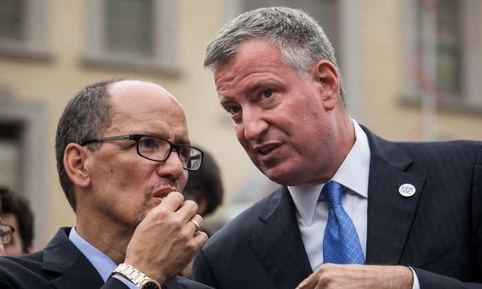 New York City Mayor Bill de Blasio (R) and Department of Labor Secretary Tom Perez speak privately at a press conference before signing an executive order raising the living wage law on September 30, 2014 in New York City (Andrew Burton/Getty Images)