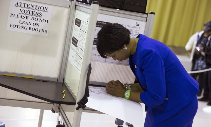 Washington Democratic mayoral candidate Muriel Bowser, right, fills out her ballot on election day at LaSalle-Backus Education Campus, on Tuesday, Nov. 4, 2014, in Washington. Bowser is favored to continue her party's unbeaten streak for the city's top office in Tuesday's election. (AP Photo/Evan Vucci)