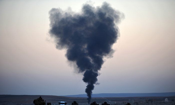 Thick smoke rises from the Syrian town of Kobani as Turkish soldiers stand guard on the Turkish side of the border during fighting between ISIL militants and Kurdish People's Protection Unit forces, as seen from the Mursitpinar crossing on the Turkish-Syrian border on Oct 26, 2014. Since mid-September, more than 200,000 people from Kobani have fled into Turkey. (Kutluhan Cucel/Getty Images)