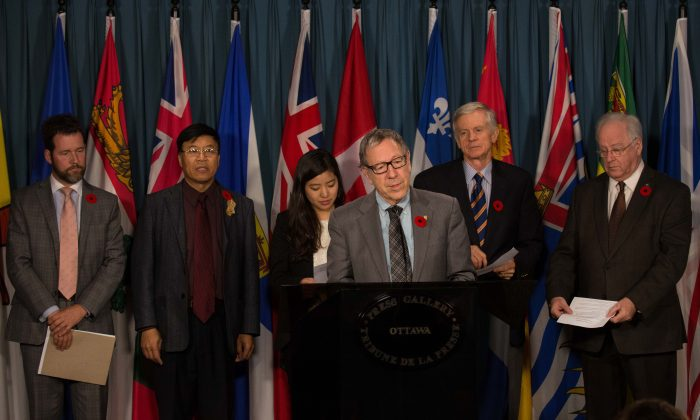 (L-R) Conservative MP Scott Reid, Wang Bingwu, Ti-Anna Wang, Liberal MP Irwin Cotler, former MP David Kilgour, and NDP MP Wayne Marston called for democracy activist Dr. Wang Bingzhang to be released from prison in China during a press conference on Parliament Hill on Nov 5, 2014. (Matthew Little/Epoch Times)