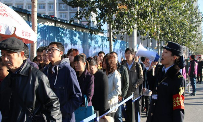 Passengers wait in line to take a subway during the ban on alternate days for odd and even license plates put in place for the APEC Summit, on November 3, 2014 in Beijing, China. Complaints among Beijing residents have grown louder concerning the inconveniences brought on by Beijing, which is seeking to make a good impression on foreign leaders. (ChinaFotoPress/Getty Images)