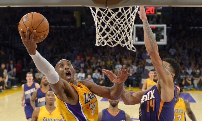 Los Angeles Lakers guard Kobe Bryant shoots as Phoenix Suns guard Gerald Green defends during the second half of an NBA basketball game, Tuesday, Nov. 4, 2014, in Los Angeles. The Suns won 112-106. (AP Photo/Mark J. Terrill)