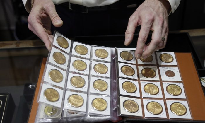 Numis International Inc. owner Jacob Notowitz displays antique gold coins at his store in Millbrae, Calif., on Nov. 5, 2014 . (AP Photo/Marcio Jose Sanchez)