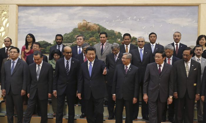 Chinese President Xi Jinping, center, shows the way to guests who attended the signing ceremony of the Asian Infrastructure Investment Bank at the Great Hall of the People in Beijing. China, Oct. 24, 2014.  (AP Photo/Takaki Yajima)