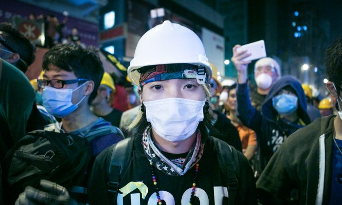A protester wearing protective gear, is standing on the front lines of a face off between protesters and police in Mong Kok, Hong Kong, on Nov. 5, 2014. (Benjamin Chasteen/Epoch Times)