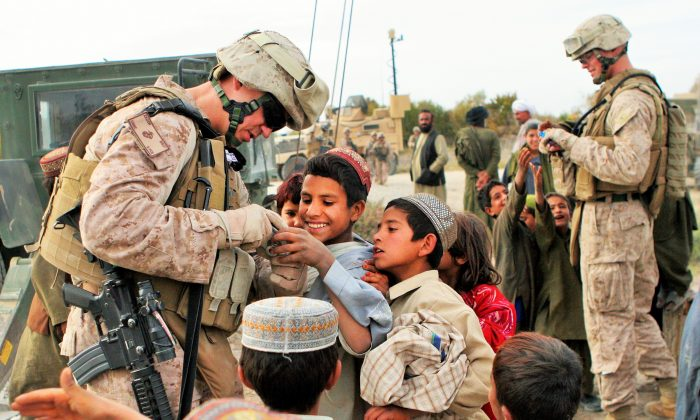 U.S. Marine Corps Master Sgt. Carl Zador interacts with Afghan children near Patrol Base Atull in Helmand Province, Afghanistan, on Nov. 20, 2011. Zabor is assigned to the 9th Engineer Support Battalion, 2nd Marine Logistics Group Forward. (Courtesy U.S. Marine Corps by Lance Cpl. Jessica S. Gonzalez)