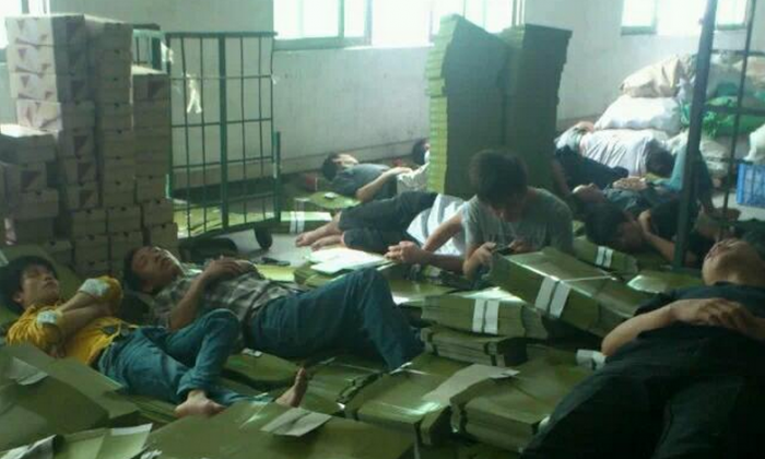 Workers at the Dongguan Xing Hong Shoe Industry sleeps on boxes at the company building in Dongguan City of Guangdong Province on Oct. 30, 2014, protesting for their salaries owed for two months. Owner of Dongguan Xing Hong has been missing for days with 700 workers unpaid for two months. (Weibo.com)