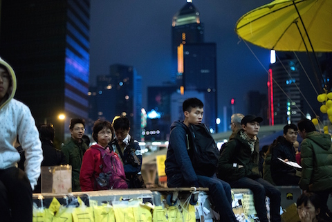 People sit on a wall as they listen to a speaker at the movement's main protest site in the Admiralty district of Hong Kong on December 6, 2014. (Johannes Eisele/AFP/Getty Images)
