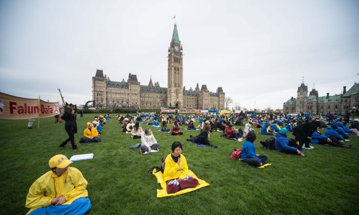 Falun Gong adherents gathered on Parliament Hill in Ottawa on Nov. 4, 2014, to call on Prime Minister Stephen Harper to address the issue of organ harvesting and the ongoing human rights abuses taking place in China when the PM meets with the Chinese leadership during his current visit to China. (Matthew Little/Epoch Times)