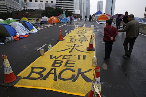 """A yellow banner reading """"We'll be back"""" is displayed by protesters at the occupied area outside government headquarters in Hong Kong Wednesday, Dec. 10, 2014. (AP Photo/Kin Cheung)"""