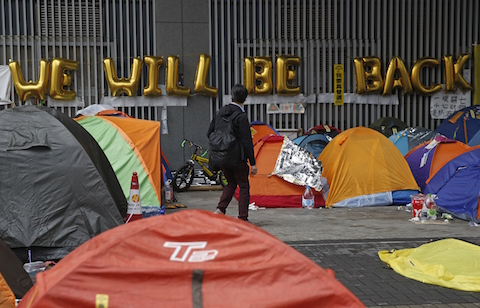 A man walks past protesters' tents on a main road at the occupied area outside government headquarters in Hong Kong Wednesday, Dec. 10, 2014. (AP Photo/Kin Cheung)