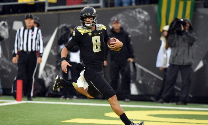 Quarterback Marcus Mariota of the Oregon Ducks is the clear front-runner to win the Heisman Trophy this season. (Steve Dykes/Getty Images)