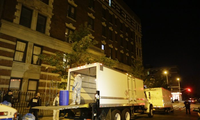 Workers from BioRecoveryCorp carry equipment from the apartment building of Ebola patient Dr. Craig Spencer in New York on Oct. 24, 2014. Spencer has been successfully treated for the virus and will be released from Bellevue hospital on Tuesday morning, city officials said. (AP Photo/Frank Franklin II)