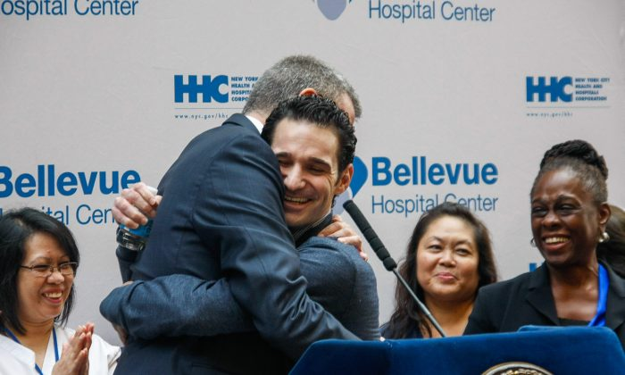 Dr. Craig Spencer (R) hugs New York City Mayor Bill de Blasio at a press conference in the lobby of Bellevue Hospital, Manhattan, New York, on Nov. 11, 2014. Spencer, who contracted Ebola while volunteering in Guinea, West Africa, was released after being cured from the deadly disease. (Epoch Times)