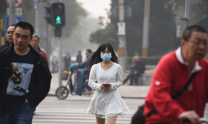 A woman wears a mask on a polluted day in Beijing on Oct. 20, 2014. Beijing resumed normal life after the APEC meetings closed on Nov. 12, 2014, as detained petitioners were released, heat was supplied, factory operations resumed, and car restrictions were lifted, and so on. (Greg Baker/AFP/Getty Images)