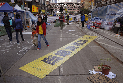 """The yellow banner reads """" I want genuine universal suffrage."""" is displayed by protesters in the Causeway Bay shopping district, one of the occupied areas in Hong Kong Saturday, Dec.13, 2014. (AP Photo/Kin Cheung)"""