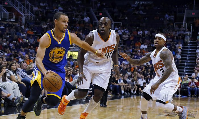 Golden State Warriors guard Stephen Curry (30) drives past Phoenix Suns forward Anthony Tolliver (40) and guard Isaiah Thomas (3) in the first quarter of an NBA basketball game, Sunday, Nov. 9, 2014, in Phoenix. (AP Photo/Rick Scuteri)