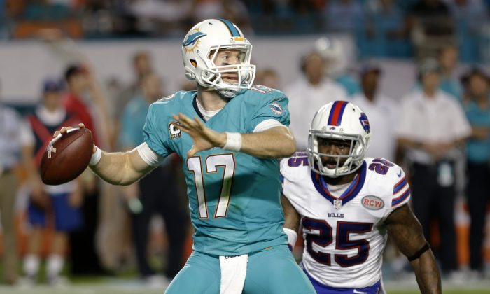 Miami Dolphins quarterback Ryan Tannehill (17) looks for an open receiver as Buffalo Bills strong safety Da'Norris Searcy (25) closes in during the first half of an NFL football game, Thursday, Nov. 13, 2014, in Miami Gardens, Fla. (AP Photo/Alan Diaz)