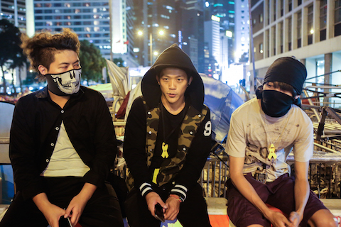 """(L-R) Homes Sin, Jack, and Victor are the main protesters in charge of organizing and guarding the barricades on the out skirts of the main """"Umbrella Square,"""" site in the Central District of Hong Kong on Oct 27, 2014. (Benjamin Chasteen/Epoch Times)"""