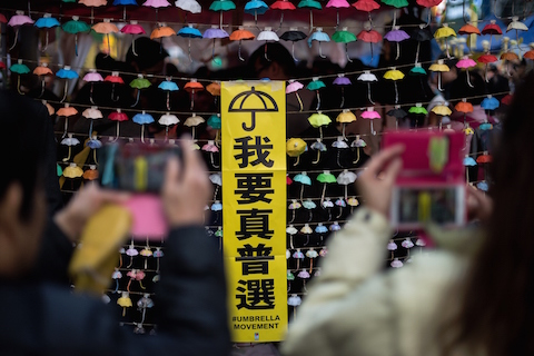 People take photos of an installation of paper umbrellas -- symbols of the pro-democracy protests in Hong Kong -- on a blockaded road in the Causeway Bay district of Hong Kong on December 14, 2014. (Alex Ogle/AFP/Getty Images)