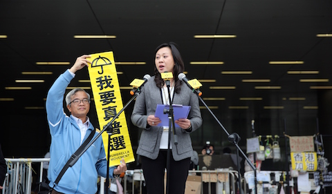 A government official (C) advises pro-democracy protesters that a deadline had ended to leave an area in front of the legislative council building in the Admiralty district of Hong Kong on December 15, 2014. (Isaac Lawrence/AFP/Getty Images)