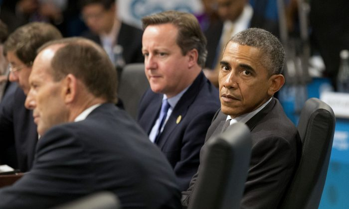 U.S. President Barack Obama, right, looks away as Prime Minister of Australia Tony Abbott, left, address a plenary session while British Prime Minister David Cameron looks on during the G-20 summit in Brisbane, Australia, Saturday, Nov. 15, 2014. (AP Photo/Rob Griffith,Pool)