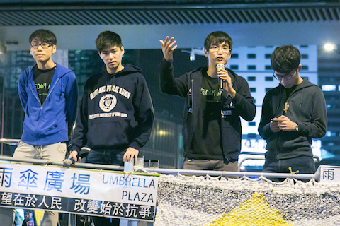 Alex Chow, secretary-general of the Hong Kong Federation of Students, along with other members, speak to large crowd of people who came to hear the students leaders talk after being denied entry into Beijing in the Central District of Hong Kong on Nov. 15, 2014. (Benjamin Chasteen/Epoch Times)