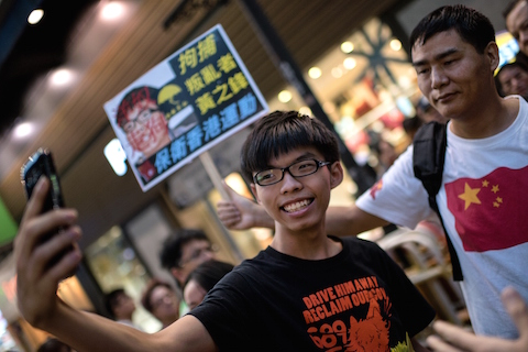 "Hong Kong student leader Joshua Wong (C) takes a ""selfie"" next to a pro-Beijing activist (R) who had been shouting slogans at Wong as he handed out flyers in support of the Hong Kong pro-democracy protests, in the Causeway Bay area of Hong Kong on November 16, 2014.  Three Hong Kong democracy protest leaders were on November 15 denied permission to board a flight to Beijing, where they had hoped to bring their demand for free elections directly to Chinese authorities. Protesters have been occupying key intersections around the former British colony calling for fully free leadership elections in 2017, but Beijing has insisted that all candidates be screened by a loyalist committee.  (Alex Ogle/AFP/Getty Images)"