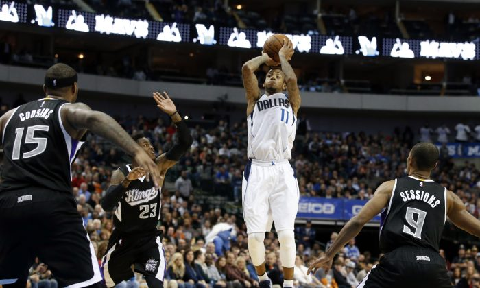 Dallas Mavericks guard Monta Ellis (11) attempts a shot as Sacramento Kings' DeMarcus Cousins (15), Ben McLemore (23) and Ramon Sessions (9) defend in the second half of an NBA basketball game, Tuesday, Nov. 11, 2014, in Dallas. (AP Photo/Tony Gutierrez)