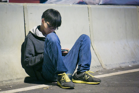 Student leader Joshua Wong sits just outside the Citic Tower area at the Admiralty protest site on Nov. 17, 2014. (Benjamin Chasteen/Epoch Times)