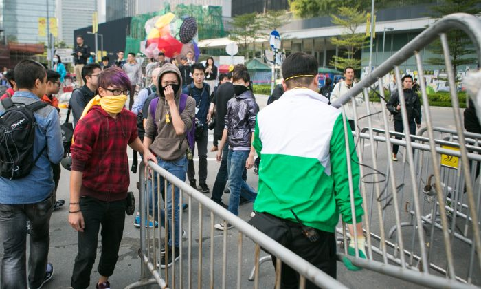 Protesters add more barricades to the area at the Citic Tower at Admiralty as police say they will clear the area after given the clearance from the high court in Hong Kong on Nov. 18, 2014. (Benjamin Chasteen/Epoch Times)